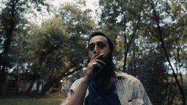 A man smokes a cigarette at dusk