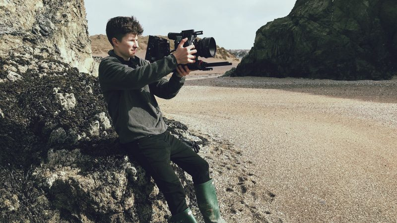 A young man sitting on a large rock in a cove. He is holding a video camera.