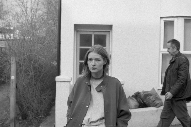 Black and white photo of a young woman with dark blond hair. She is outside a house and is wearing a bomber jacket.