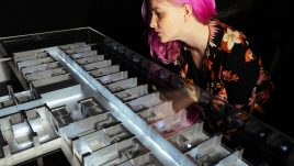A woman with pink hair looks at a model of a hotel room made from metal