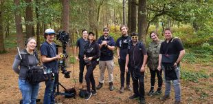 A group of camera crew standing in a woodland area with camera equipment