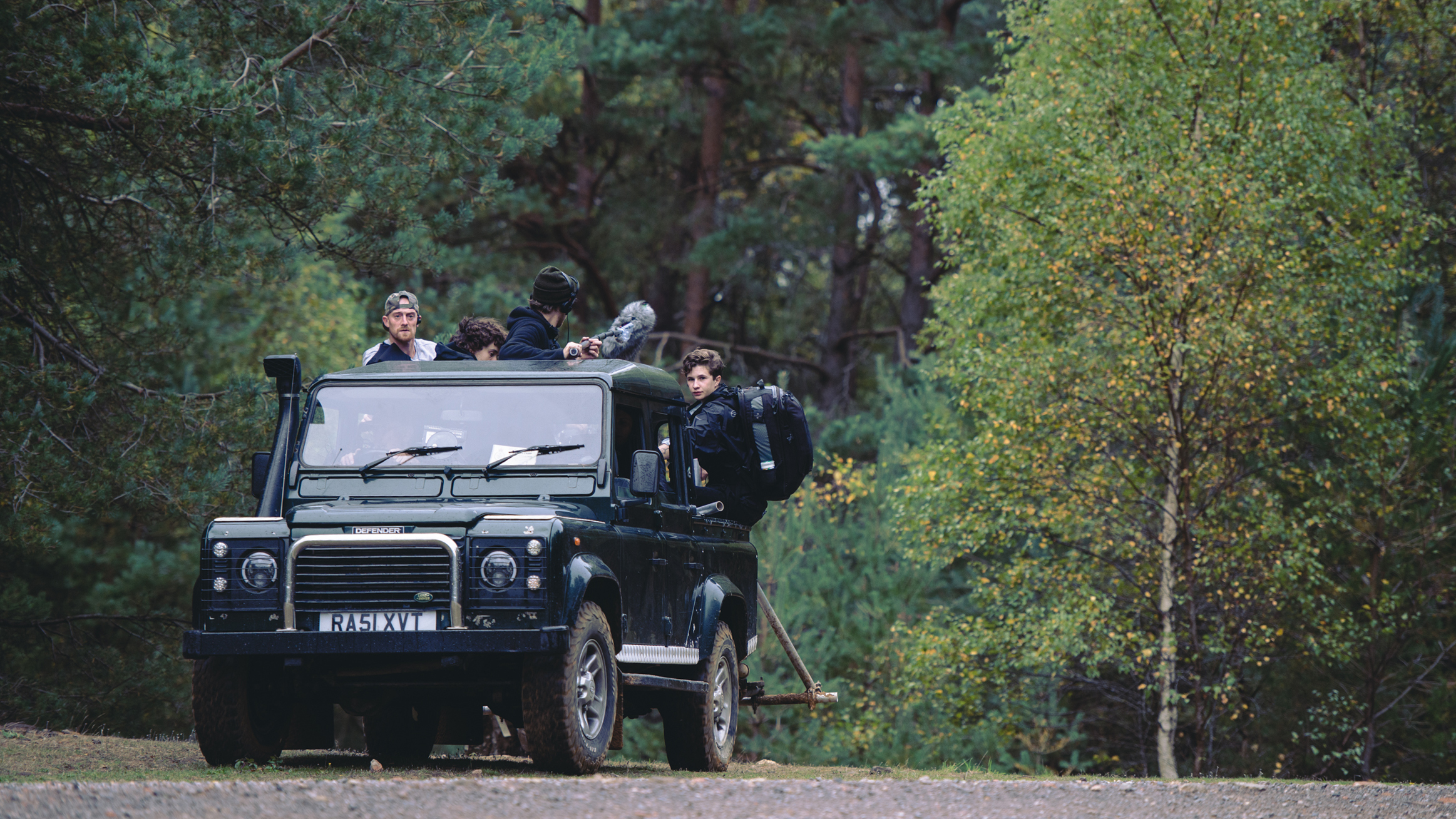 A jeep driving through a wooded area with a film crew sitting on the back