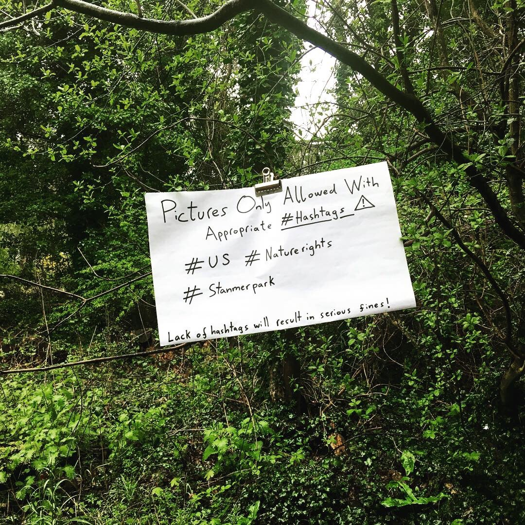 A note clipped to a tree in the woods reads 'Pictures only allowed with appropriate hashtags'.