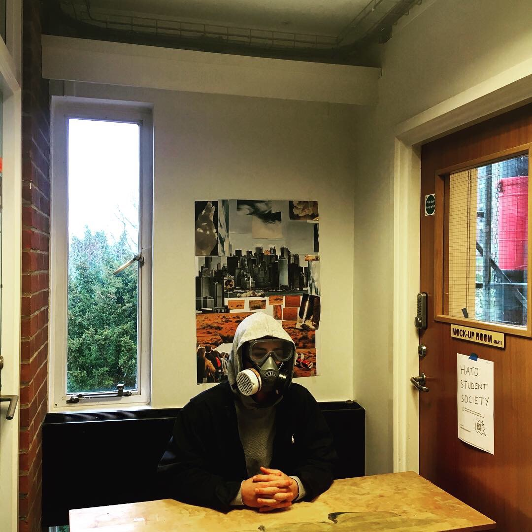 A student from the University of Sussex sits at a desk wearing a hood and a gas mask.