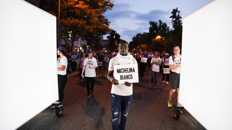 An image of a Philadelphia street at dusk, showing a float made up of two large light panels and between them a black male, dressed in blue jeans and a white t-shirt, holding up a white sign reading the name Michelina Bianco in big capital letters. Behind him are more people walking in the parade, each holding a sign with a different name. They are taking part in Spit Spreads Death: The Parade, in honour of 1918 flu victims.
