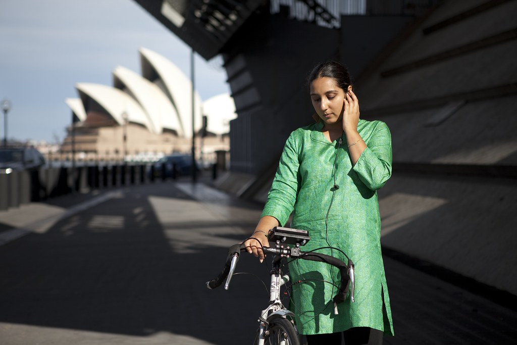 A person standing next to a bike, wearing a longline top, looks down at a smartphone mounted on their bike, with their left hand holding headphones to one ear. The Sydney Opera House appears behind them slightly out of focus.