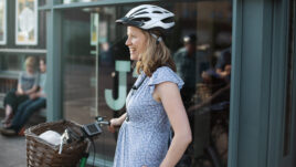 A woman in her 30s smiling in a cycling helmet standing over her bicycle, which has a digital tablet on the handlebars