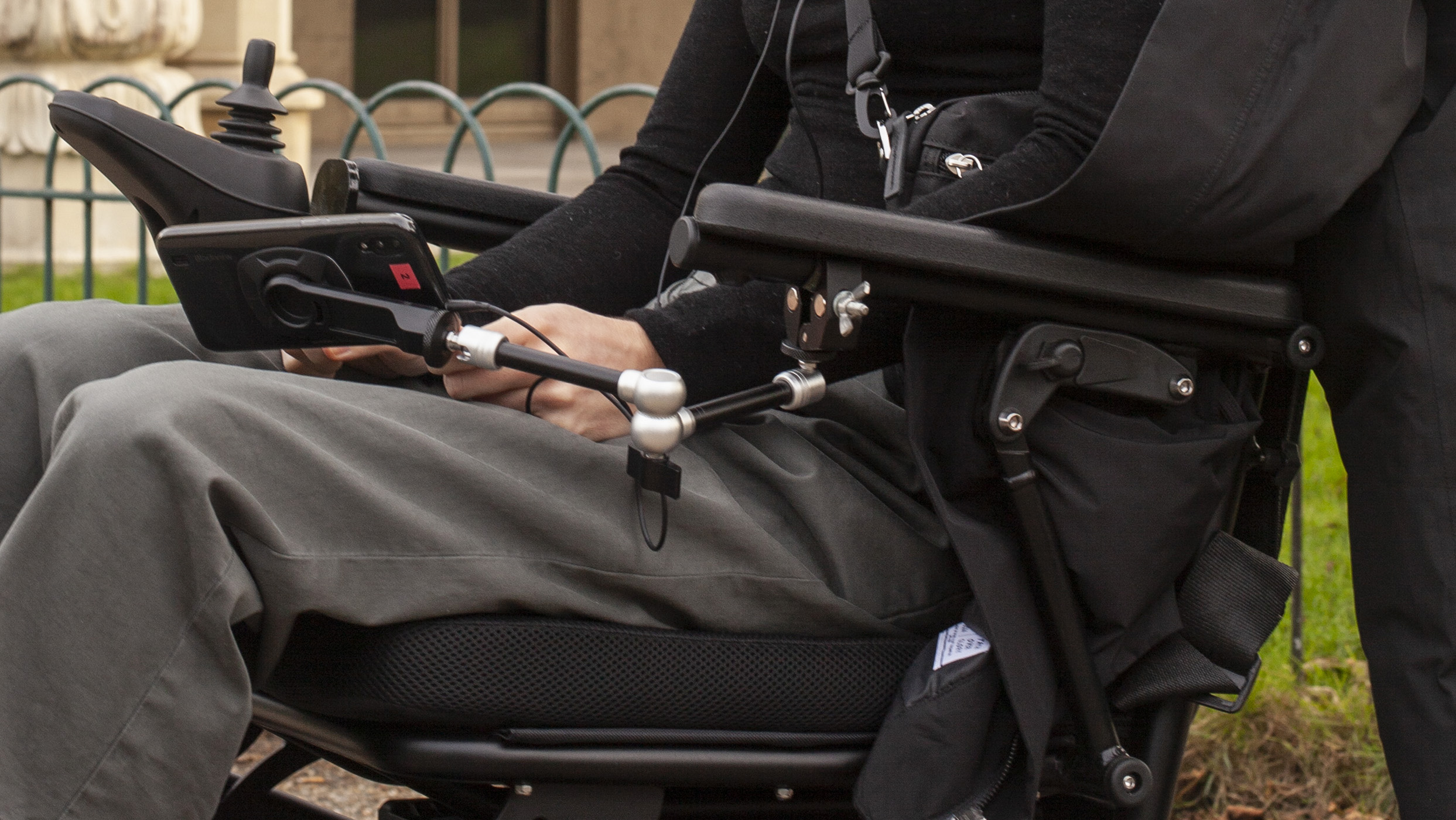 A white person in an electric wheelchair with a phone mounted to the chair