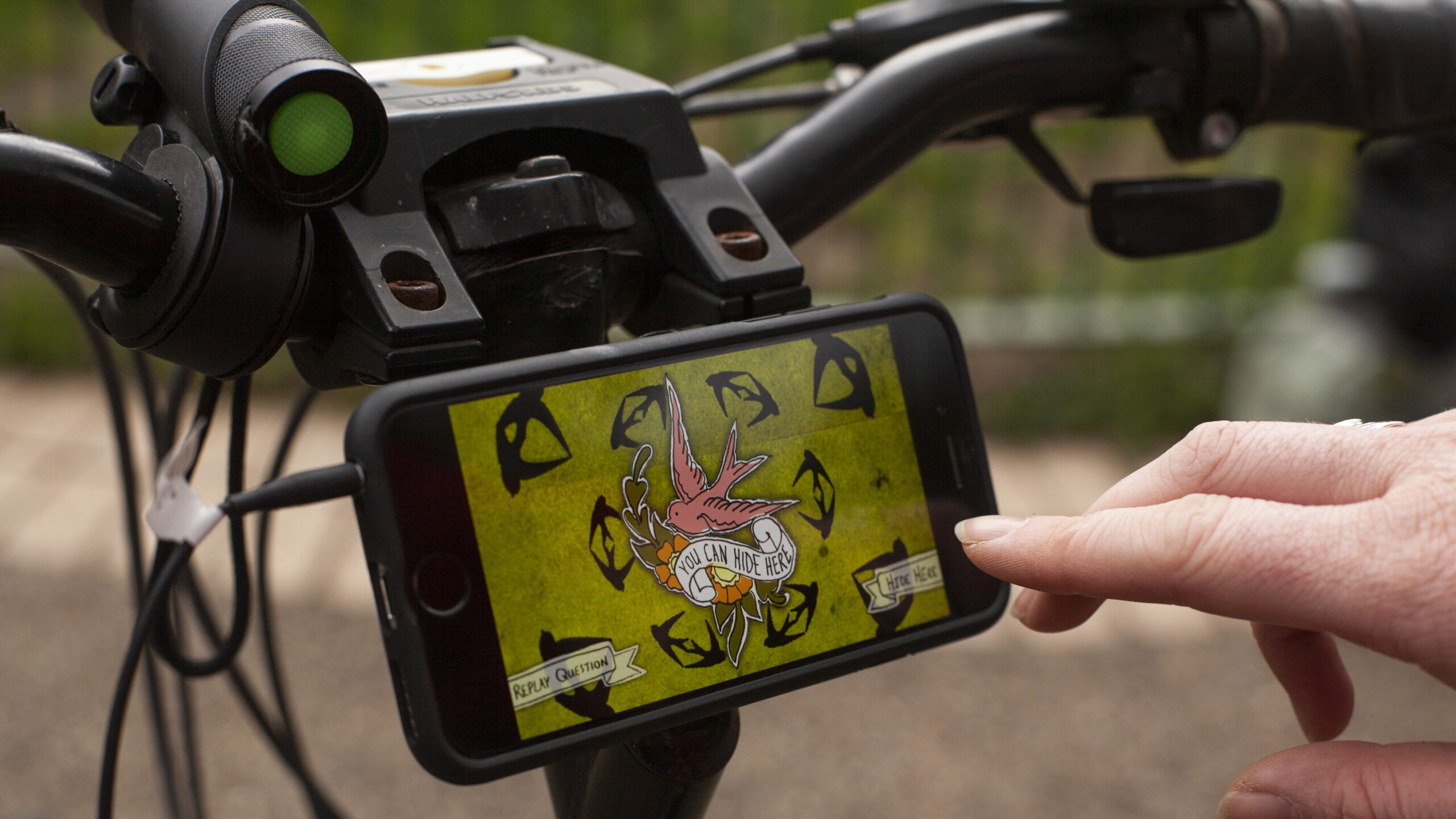 A phone mounted to an bike with a white person tapping the screen