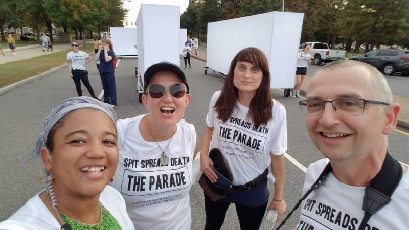 Four people stand together in the sunshine in Philadelphia, all wearing t-shirts saying 'Spit Spreads Death: the Parade'. From left to right we see a brown-skinned woman, smiling; a white woman in sunglasses and a cap, smiling; a white woman with long brown hair, smiling; a white man with glasses and a camera around his neck, smiling.