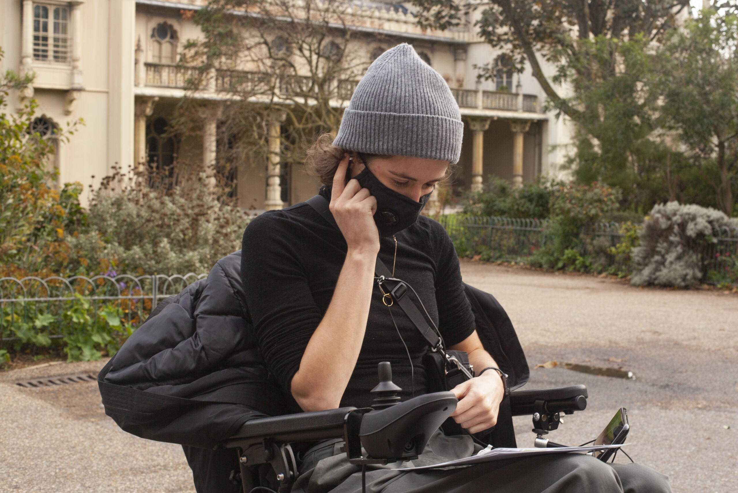 A white person in an electric wheelchair wearing a black face mask, black top and grey beanie hat looks down at a smartphone mounted on their chair, with their right hand holding headphones to one ear.