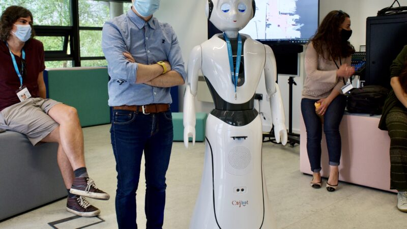 Blast Theory artist Nick, wearing a mask, hat, shirt and trousers, stands cross-armed next to a human-sized white robot with human facial features, arms and a circular body.