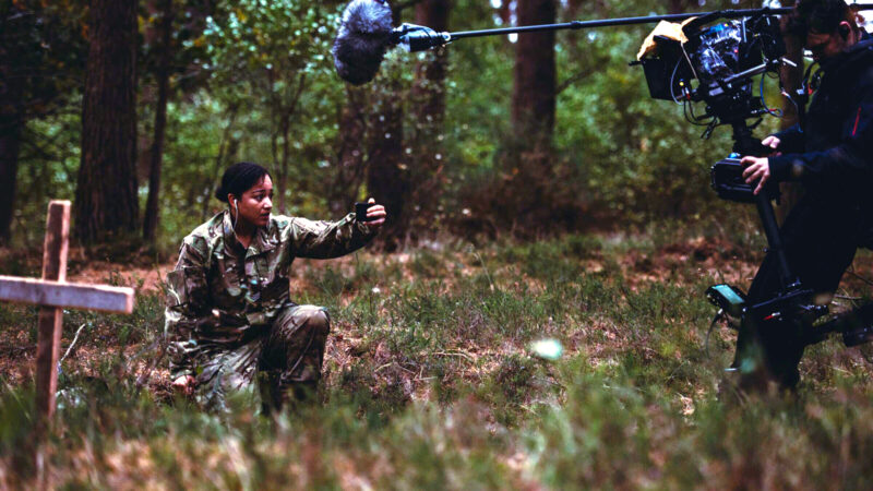 A person dressed in camouflage, kneels on the floor holding their phone up in front of their face. A sound and camera crew stand over them with their equipment in view. In front of the camouflaged person is a wooden cross stuck in the ground.