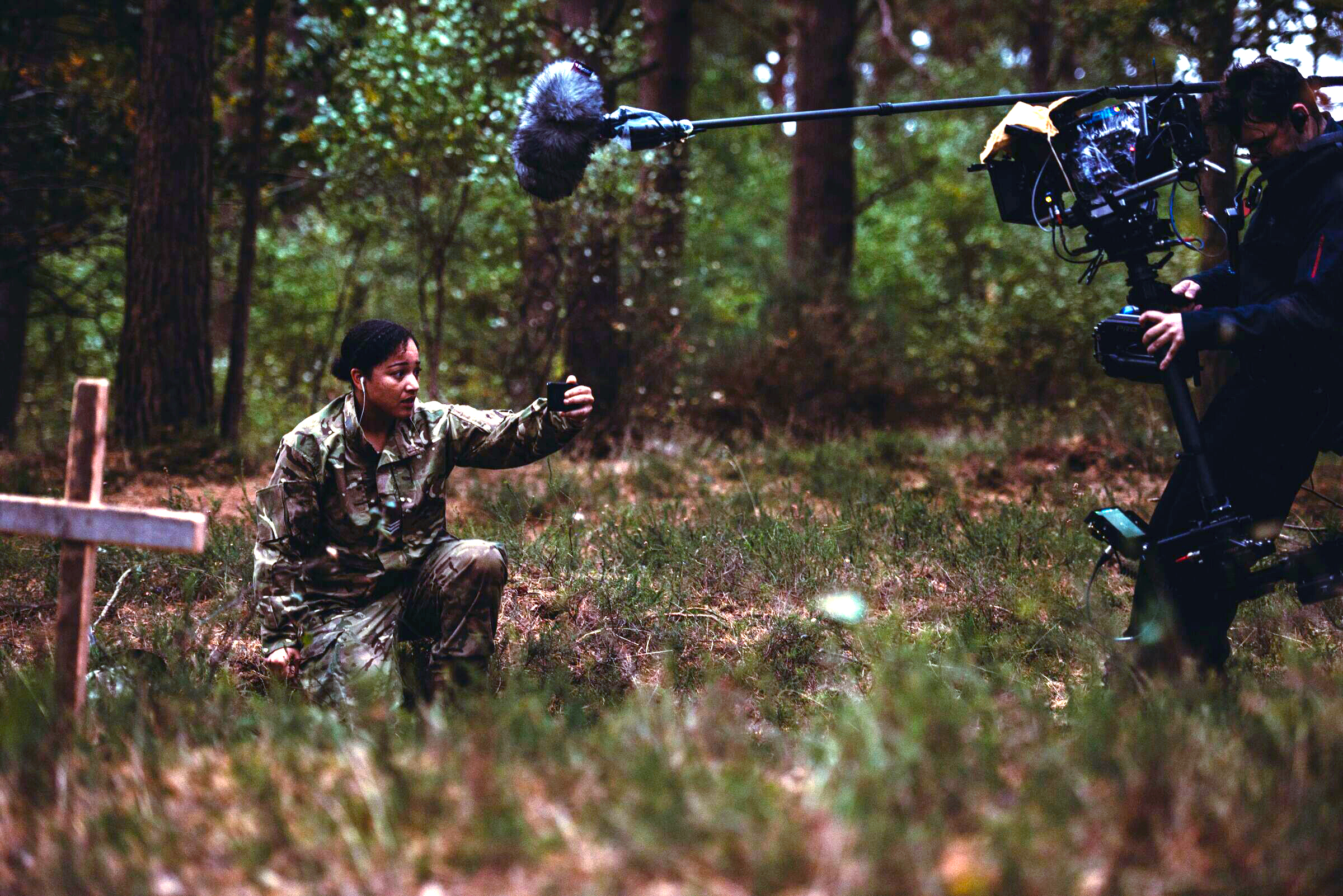Equality Action Plan Image. A person dressed in camouflage, kneels on the floor holding their phone up in front of their face. A sound and camera crew stand over them with their equipment in view. In front of the camouflaged person is a wooden cross stuck in the ground.