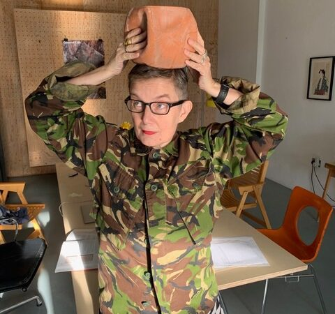 Artist Ju is wearing a camouflage jacket with a black and white abstract top underneath. She is holding a plant pot on top of her head and is staring off into the distance.